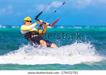 young smiling kitesurfer on sea background - stock photo