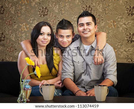 Young smiling Latino family sitting indoors together - stock photo