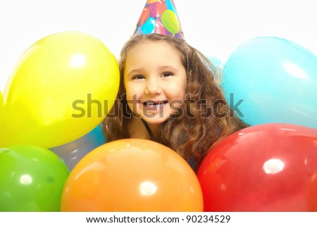 Young smiling little girl in dressing gown celebrates her birthday colorful balloons isolated on white