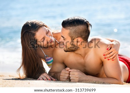 Young smiling lovers sunbathing at sandy beach in vacation