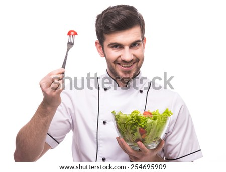 Young, smiling male chef is eating salad isolated on white background. - stock photo