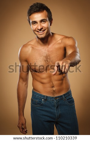 Young smiling male shirtless pointing at you, over beige background