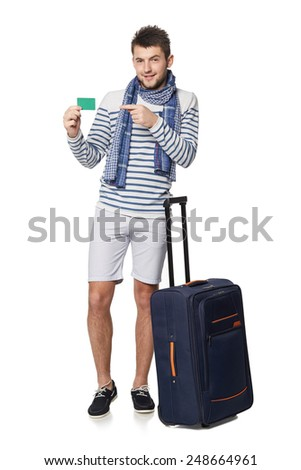 Young smiling male with suitcase showing empty credit card, isolated on white background - stock photo