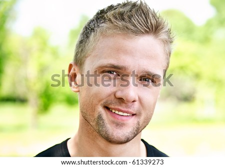 Young smiling man against summer park. - stock photo
