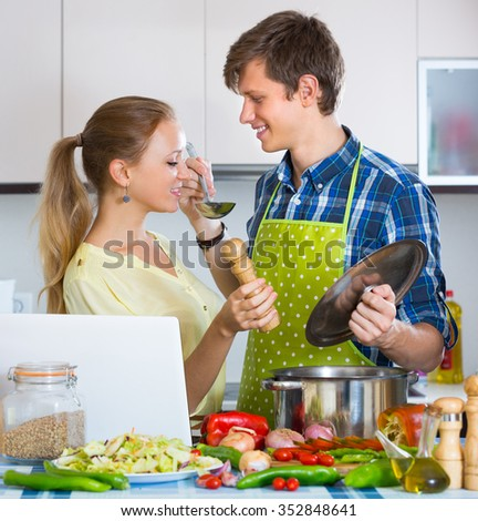 Young smiling man and woman at home kitchen cooking with laptop on the table