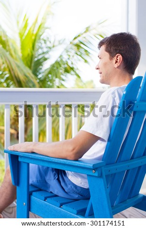 young smiling man enjoying summer vacation in the lounge chair at terrace