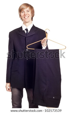 Young smiling man holding a hanger - stock photo