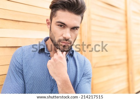young smiling man holding his chin on his hand looking at the camera - stock photo