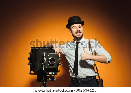 Young smiling man in hat as photographer with retro camera on an orange background - stock photo