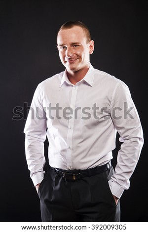 Young smiling man in white shirt over dark background - stock photo