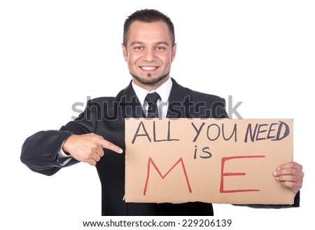 Young smiling man is holding sign All you need is me. He is looking for a job. - stock photo