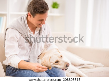 Young smiling man is playing with his dog sitting on sofa. - stock photo