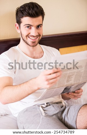 Young, smiling man is reading a newspaper, sitting on bed at morning. - stock photo