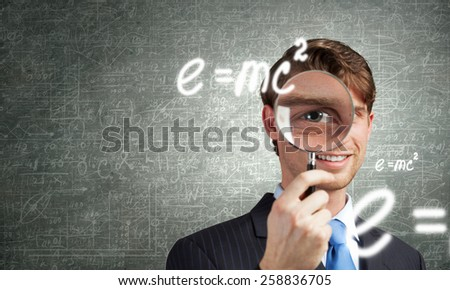 Young smiling man looking in magnifying glass