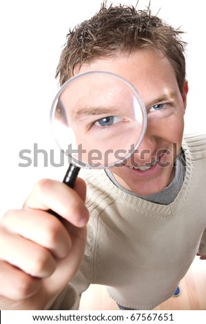 young smiling man looking through magnifying glass isolated over white background - stock photo