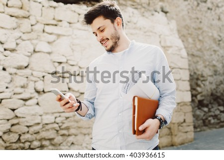 Young smiling man outdoor potrait in a sunny day making call with sketch construction project in his hands  - stock photo