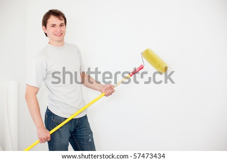 young smiling man painting a wall - stock photo