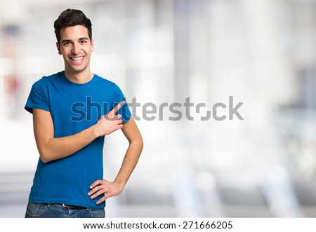 Young smiling man pointing his finger to the copyspace - stock photo