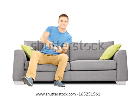Young smiling man seated on a sofa playing video games isolated on white background - stock photo