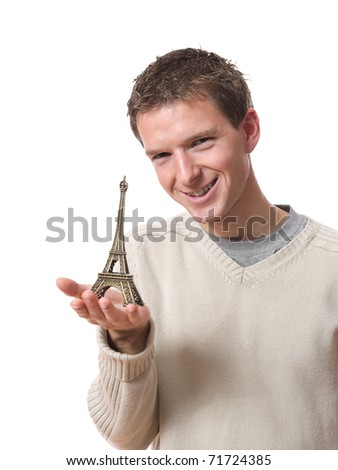 young smiling man showing tiny Eiffel tower isolated over white background - stock photo