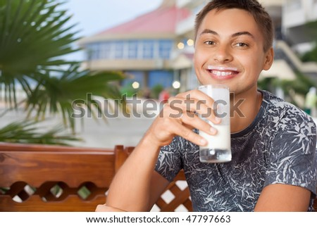young smiling man sitting in an arbors on resort, drinking kefir