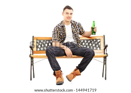 Young smiling man sitting on a bench and holding a beer bottle, isolated on white background - stock photo