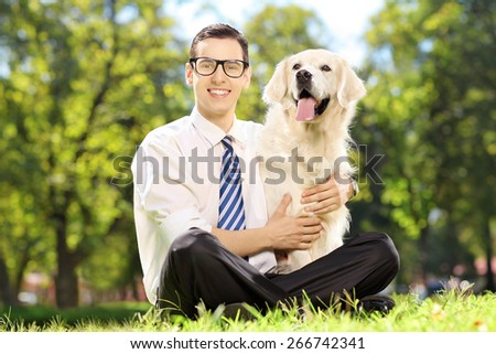 Young smiling man sitting on a green grass and hugging his labrador retriever dog in a park - stock photo