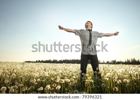 Young smiling man standing on a meadow with dandelions on a blue sky background - stock photo
