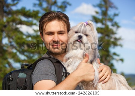 Young smiling man tourist with shih-tzu dog portrait. Showing thumbs up handsign. - stock photo