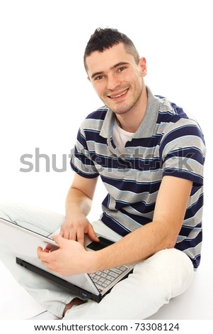 Young smiling man with a laptop - stock photo