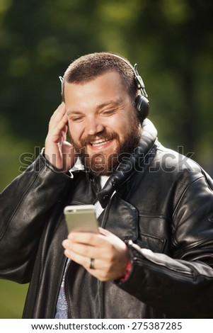 Young smiling man with beard holding a smart mobile phone and headphones - stock photo
