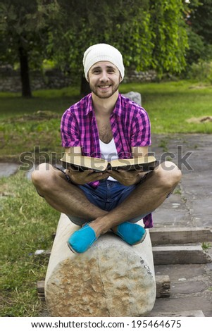 Young smiling man with book in hands - stock photo