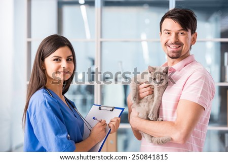 Young smiling man with his cute cat on a visit to the vet. - stock photo