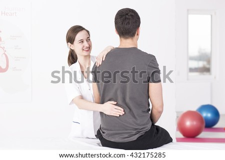 Young, smiling masseur giving a back massage to her patient sitting on a massage table - stock photo