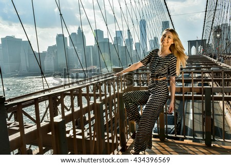 Young smiling model with long blonde hair posing at the bridge in hot summer day wearing fashionable jumpsuit.