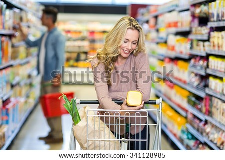 Young smiling mother doing shopping at supermarket - stock photo
