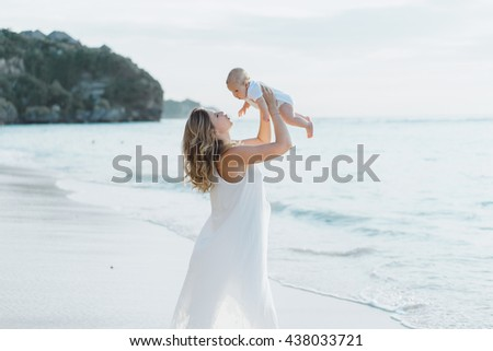 young smiling mother in flying white dress with her baby on the beach . Mother holds newborn baby in her arms . Happy woman with a child smiling and kissing her baby. close up portrait out door - stock photo