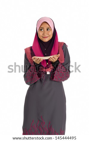 Young smiling muslimah standing and holding on a plate isolated on white background - stock photo
