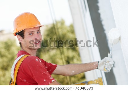 Young smiling painting facade builder worker with roller in work wear - stock photo