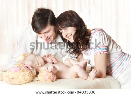 Young smiling parents looking at baby, play with child. Indoor. - stock photo