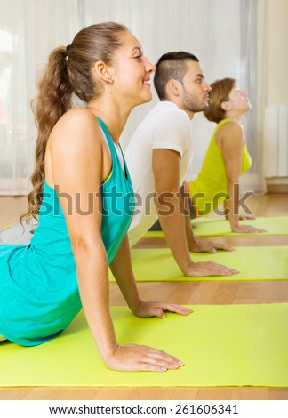 Young smiling people doing yoga on mats in gym - stock photo