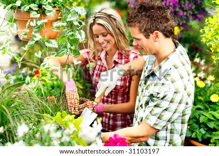 Young smiling people florists working in the garden - stock photo