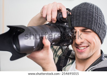 Young smiling photographer is using professional camera on gray background.