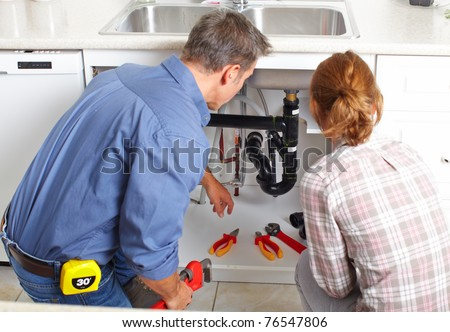 Young smiling plumber repairing sink in kitchen. - stock photo