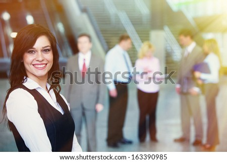 Young smiling pretty bussinesswoman over team background - stock photo