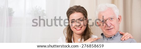 Young smiling pretty caregiver and senior happy male patient - stock photo