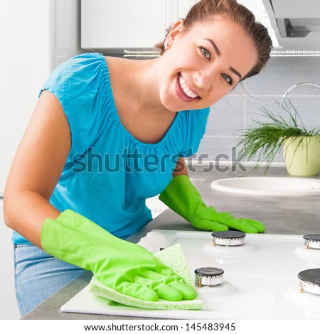 young smiling pretty woman cleans the kitchen at home - stock photo