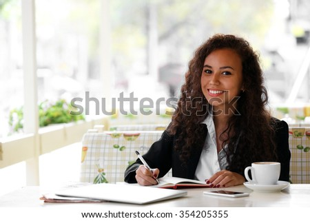 Young smiling pretty woman makes notation at the restaurant's terrace - stock photo