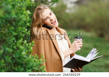 Young smiling pretty woman talking on cell phone, against background of spring park. - stock photo
