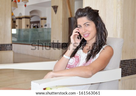 Young smiling pretty woman talking on her mobile phone in the hotel lobby
